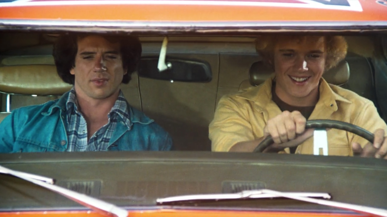Bo (right) and Luke (left) Duke in their car, the General Lee.